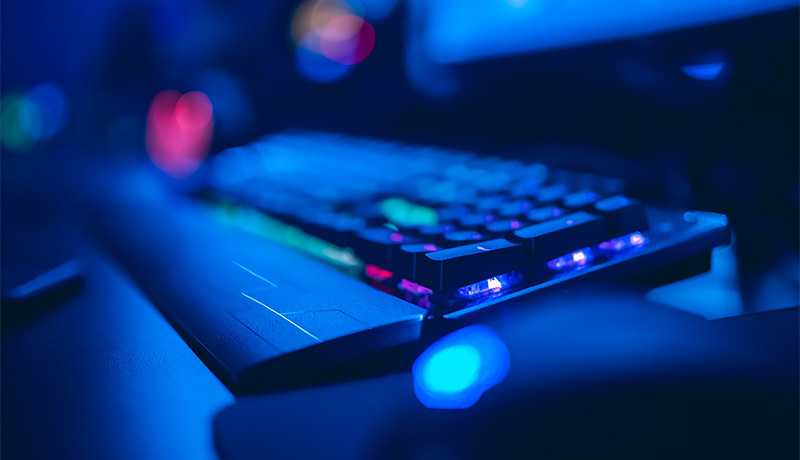 An LED lit keyboard and monitor in a dimly lit gaming room