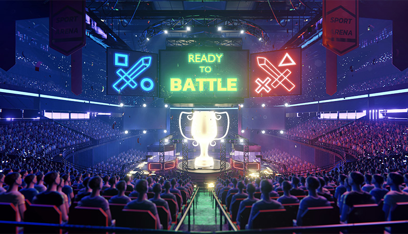 A wide interior view of a fictional esports arena packed with fans. A sign above the player area says Ready to Battle.